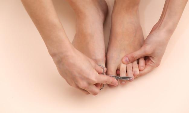 Frau schneidet zehennägel mit maniküre-schere auf beigem hintergrund. self-care-konzept