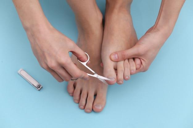 Frau schneidet zehennägel mit maniküre-schere auf blauem hintergrund. self-care-konzept
