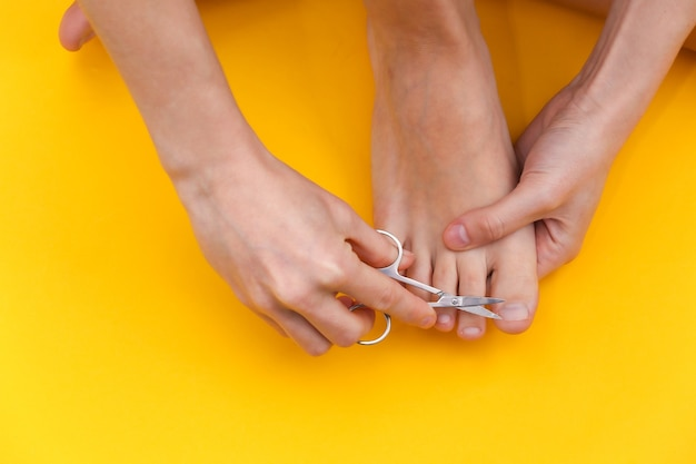 Frau schneidet zehennägel mit maniküre-schere auf gelbem hintergrund. self-care-konzept