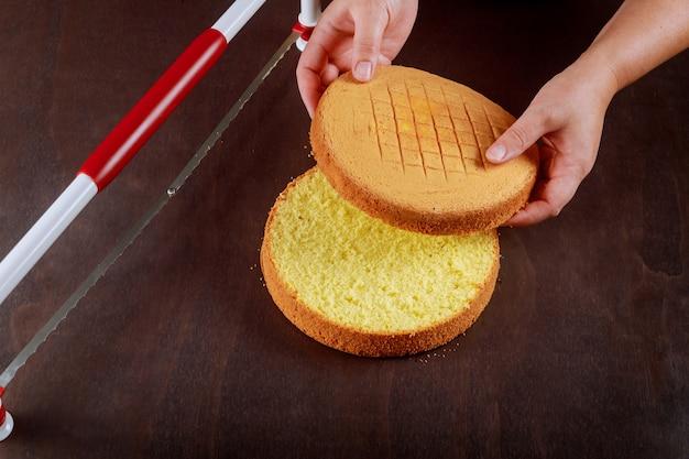 Frau schnitt die oberseite des kuchens mit einem gezackten richterkuchen