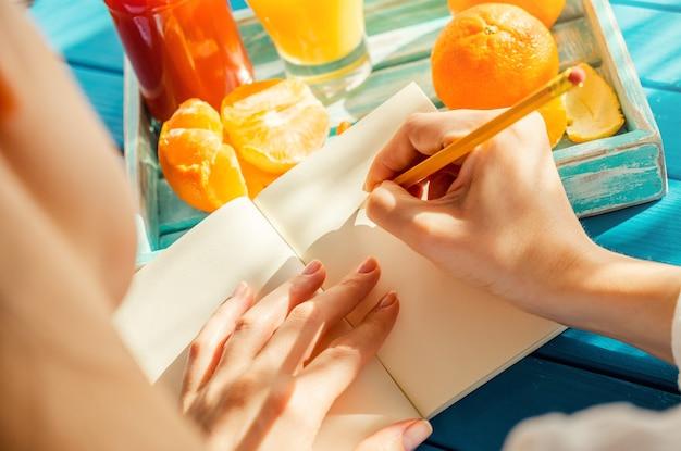 Frau schreibt am sonnigen morgen in ihr notizbuch
