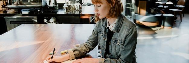 Frau schreibt auf ihrem notizbuch in einem café