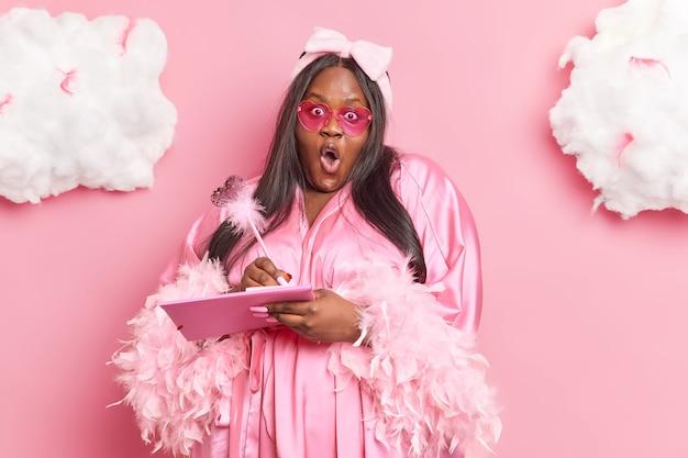 Frau schreibt ideen in notizbuch macht liste zu tun starrt erstaunt hält den mund offen trägt lässigen morgenmantel trendige rosa sonnenbrille