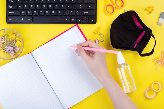 Frau schreibt im notizbuch am schreibtisch, neben antiseptikum und maske, gelber hintergrund.