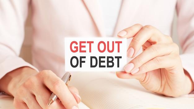 Frau schreibt in ein notizbuch mit einem silbernen stift und einer handhaltekarte mit text: get out of debt
