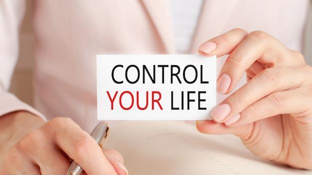 Frau schreibt in ein notizbuch mit einem silbernen stift und einer handhaltekarte mit text: kontrollieren sie ihr leben.
