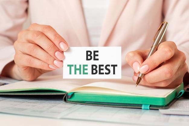Frau schreibt in ein notizbuch mit einem silbernen stift und einer handhaltekarte mit text: seien sie der beste