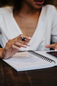 Frau schreibt in ihr notizbuch