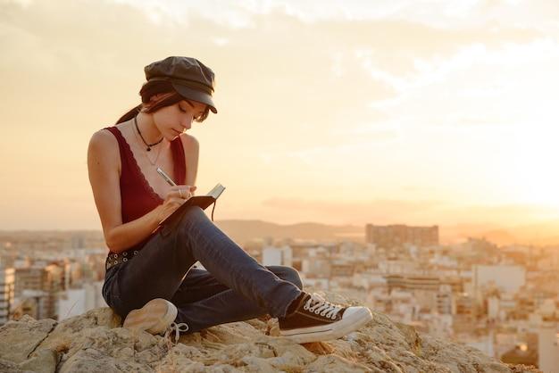 Frau schreibt in ihrem notizbuch sätze und gedanken im freien bei sonnenuntergang