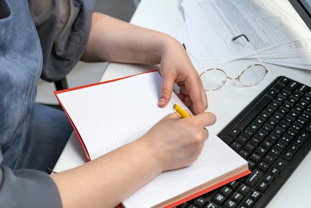 Frau schreibt in notebook am arbeitsplatz. buchhalter bei der arbeit. taskmanager. aufgaben planen.