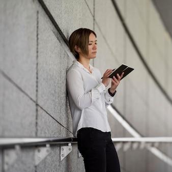 Frau schreibt in notizbuch mittlerer aufnahme
