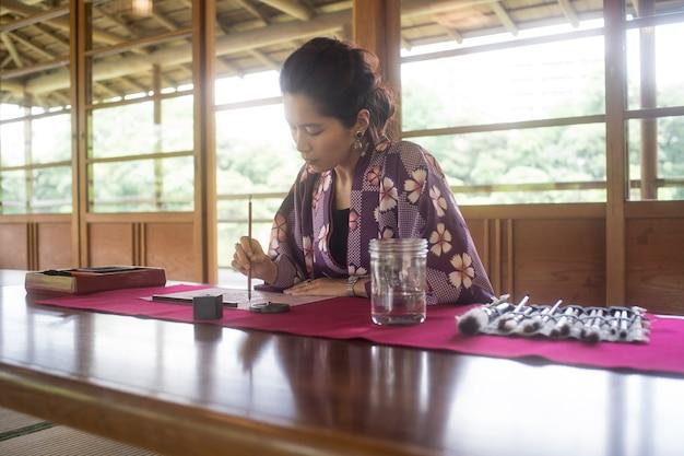 Frau schreibt mit tinte auf japanpapier