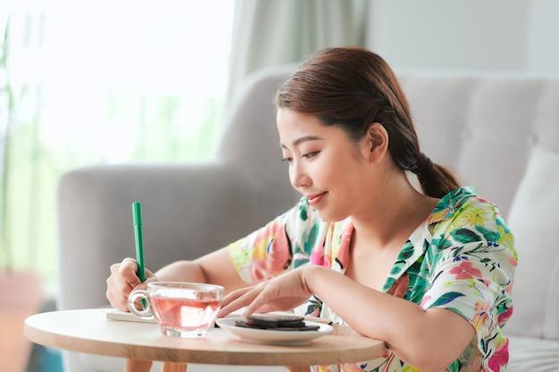 Frau schreibt notizen in eine agenda oder ein tagebuch, die zu hause auf einer couch im wohnzimmer sitzt living