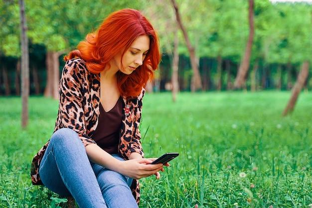Frau schreibt sms, während sie auf dem gras sitzt.