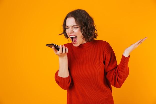 Frau schreit beim telefonieren auf gelb