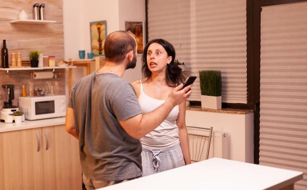 Frau schreit jelousigen ehemann wegen missverständnissen mit texten vom telefon an. frustriert beleidigt irritiert beschuldigt frau der untreue, argumentiert sie mit nachrichten.