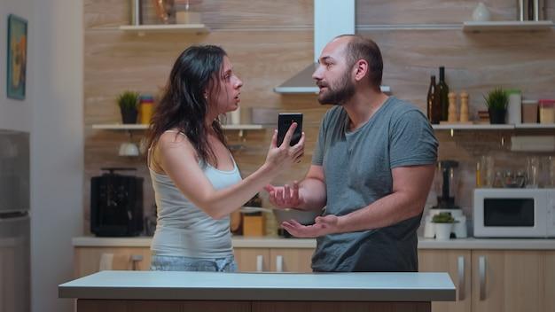 Frau schreit untreuen ehemann in der küche an. eifersüchtige frau betrog wütend frustriert beleidigt irritiert und beschuldigte ihren mann der untreue und zeigte ihm nachrichten auf dem smartphone, die verzweifelt schreien.