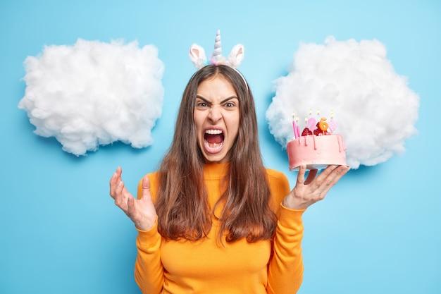 Frau schreit wütend gesten aktiv schreit laut hält festlichen leckeren kuchen trägt orangefarbenen pullover posen auf blau
