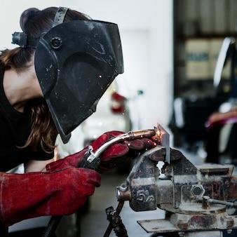 Frau schweißt ein metallstück in der garage