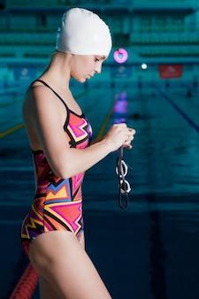 Frau schwimmer in einer badekappe kleidet brille und bereit zu schwimmen