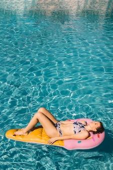 Frau schwimmt auf aufblasbare matratze im pool
