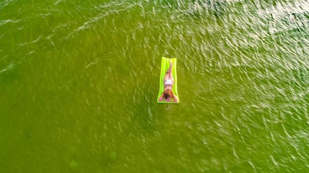 Frau schwimmt auf dem meer auf einer matratze, die das meer betrachtet