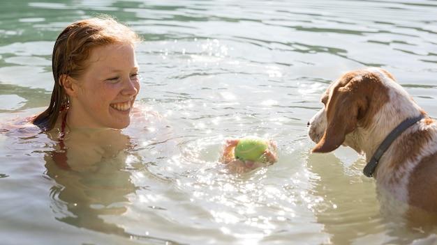 Frau schwimmt und spielt mit hund im sonnenlicht