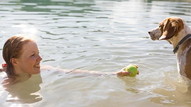 Frau schwimmt und spielt mit hundeseitenansicht