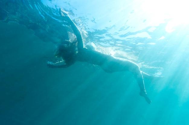 Frau schwimmt unter dem ozean