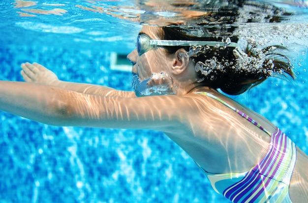 Frau schwimmt unter wasser im schwimmbad, glücklich aktive teenager mädchen taucht und hat spaß unter wasser, kind fitness und sport im familienurlaub im resort