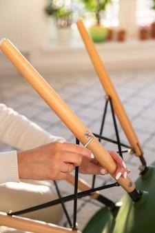 Frau selbst montiert einen sessel und zieht lose schrauben mit einem möbelsechskantschlüssel fest