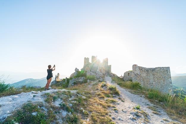 Frau selfie an burgruine auf berggipfel bei rocca calascio, italienisches reiseziel, wahrzeichen im nationalpark gran sasso, abruzzen, italien. die sonne des klaren blauen himmels platzte im gegenlicht