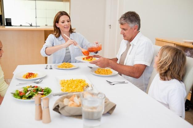 Frau serviert abendessen an familie