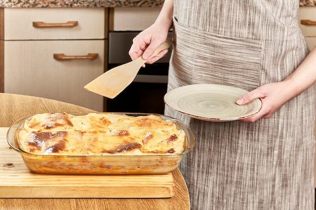 Frau serviert mit einem holzspatel eine frisch gebackene lasagne in einem teller