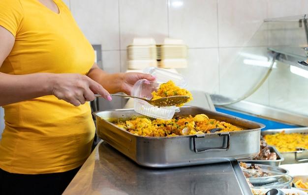 Frau serviert paella im lebensmittelgeschäft