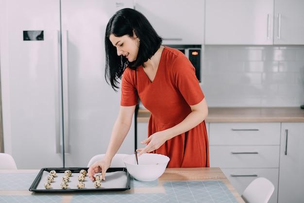 Frau setzt auf backblech rohe kekse vor dem backen in der küche