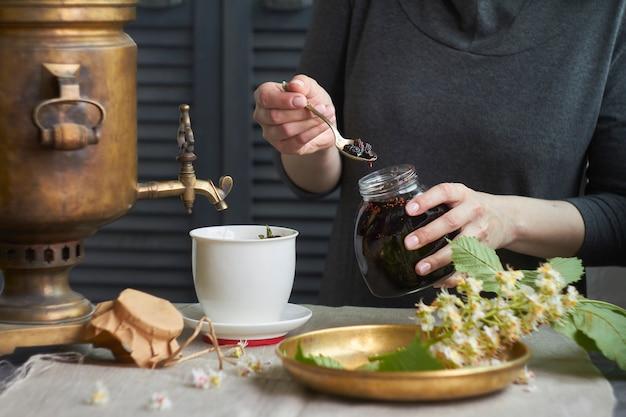 Frau setzt hausgemachte marmelade in tasse tee von samowar