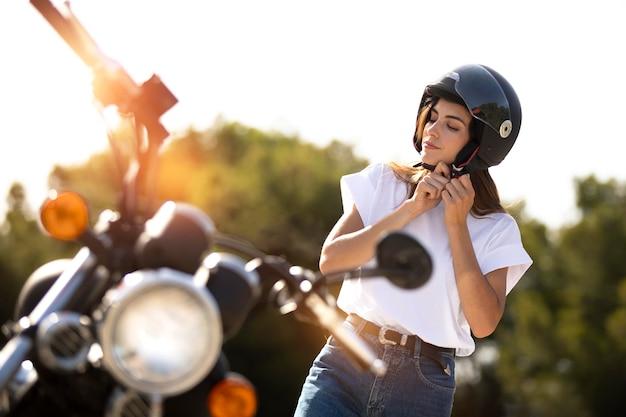 Frau setzt helm für einen motorrad-roadtrip auf