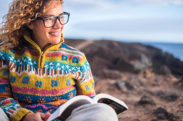 Frau setzt sich auf die felsen an einem schönen ort im freien mit ozean, liest ein papierbuch und genießt die freiheit und die entspannungssituation