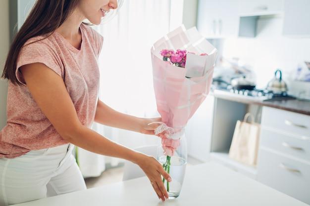 Frau setzt vase mit blumen. hausfrau kümmert sich um gemütlichkeit in der küche. modernes küchendesign