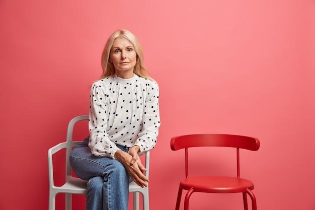 Frau sieht gut aus und posiert gut gekleidet auf einem bequemen stuhl, der allein in der warteschlange wartet, isoliert auf leuchtendem rosa