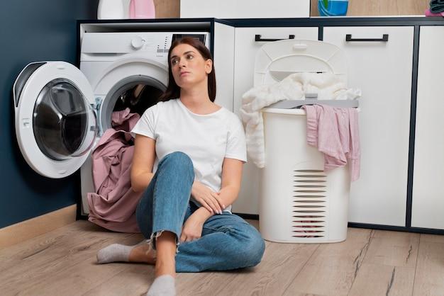 Frau sieht müde aus, nachdem sie die wäsche gewaschen hat