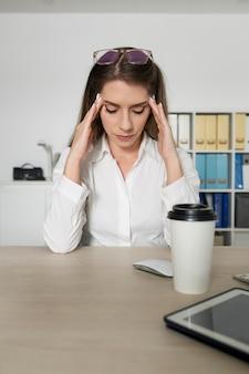 Frau sieht müde bei der arbeit aus, weil sie viel zeit am telefon verbracht hat