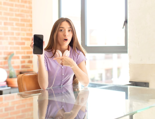 Frau sieht ungläubig aus, zeigt auf ein objekt an der seite und sagt wow, unglaublich