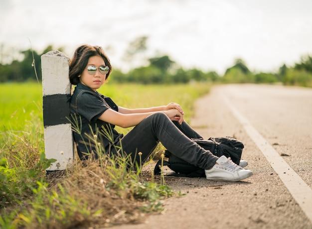 Frau sitzen mit dem rucksack, der entlang einer straße in der landschaft per anhalter fährt