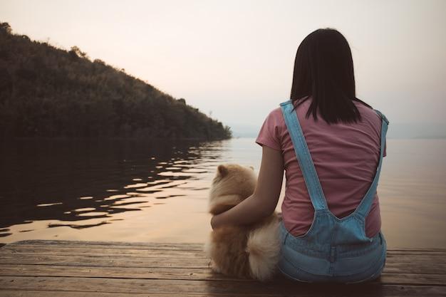 Frau sitzen und entspannen sich mit ihrem hund bewundern den sonnenuntergang himmel und den see.