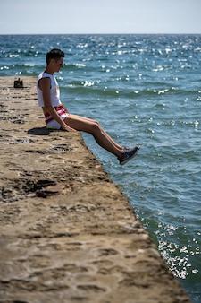 Frau sitzt allein auf dem pier in shorts und unterhemd mit schuhen. rückansicht. sommer meer