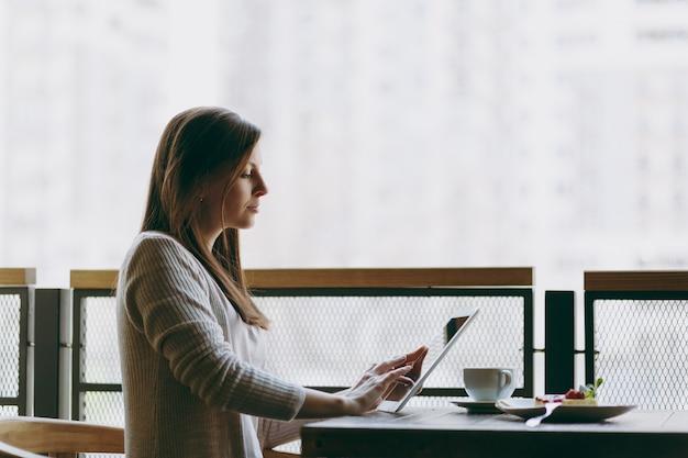 Frau sitzt allein in der nähe eines großen fensters im café am tisch mit einer tasse cappuccino, kuchen, entspannt sich in der freizeit im restaurant. frauen, die an pc-tablet-computer-rest im café arbeiten. lifestyle-konzept.