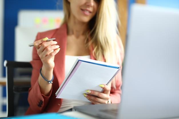 Frau sitzt am arbeitsplatz mit notizbuchstift in ihren händen. online-berufsbildungskonzept
