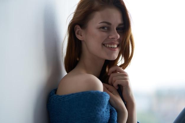 Frau sitzt am fenster mit einem blau karierten lächeln zu hause